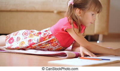 Little girl draws pictures lying on the floor