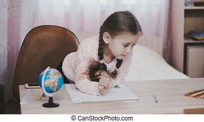 little girl draws sitting at table