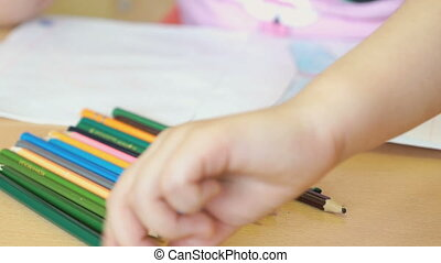 Little girl draws the pictures in the copybook - Little girl...