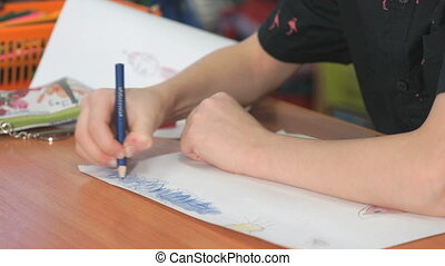 Little girl draws the pictures using color pencils -...