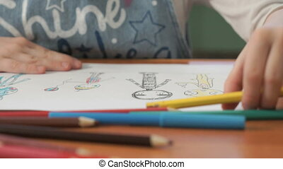 Little girl draws the pictures using color pencils - Close-...