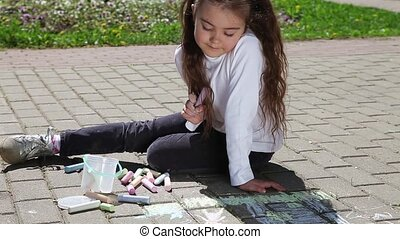 Little girl draws with chalks