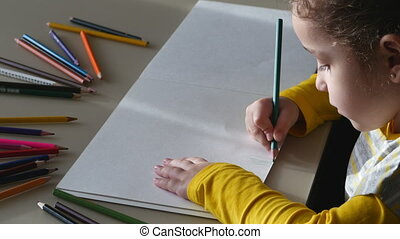 little girl draws with colored pencils. 4K.