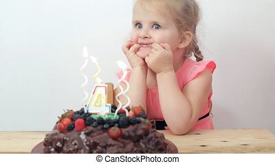 Little girl dreaming and blows out candles