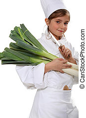 little girl dressed as a chef holding bunches of leeks