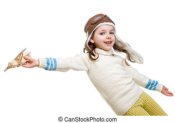 little girl dressed as pilot and playing with wooden airplane to