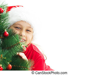 little girl dressed as Santa hugging a decorated Christmas tree