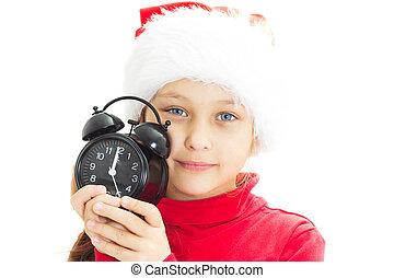 little girl dressed as Santa is holding alarm clock on white bac