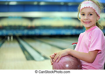 Little girl dressed in pink T-shirt sits and holds ball in...