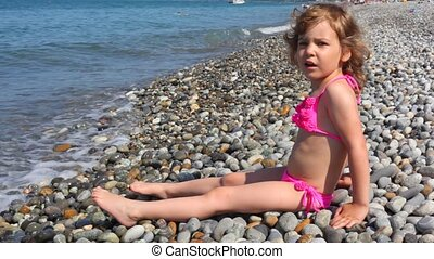 little girl dressed in swimsuit sitting in pebble beach near sea surf