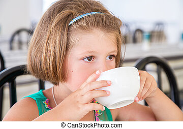 Little girl drinking a cup of milk at breakfast