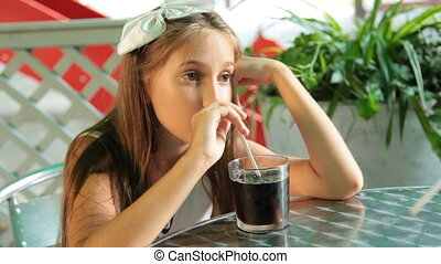 Little girl drinking cola drink at outdoor cafe