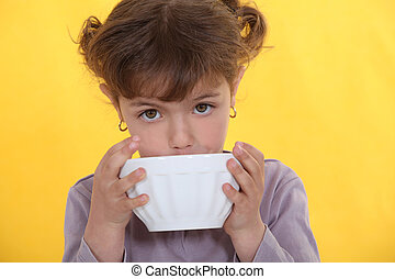 Little girl drinking from bowl