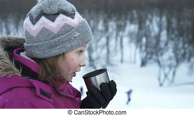 Little girl drinking hot drink outdoors in winter day