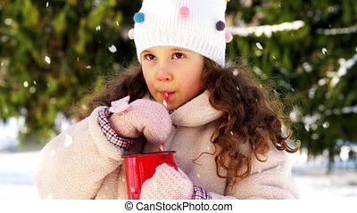 childhood, leisure and season concept - happy little girl drinking hot tea from red cup with paper straw in winter park over snow falling