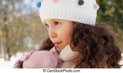little girl drinking hot tea in winter park - childhood, ...
