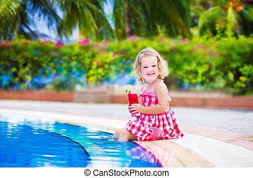Little girl drinking juice at a swimming pool - Beautiful...