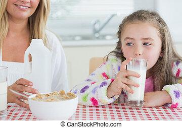 Little girl drinking milk at the kitchen