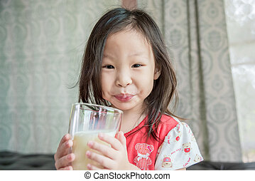Little girl drinking milk from glass