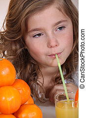 Little girl drinking orange juice through straw