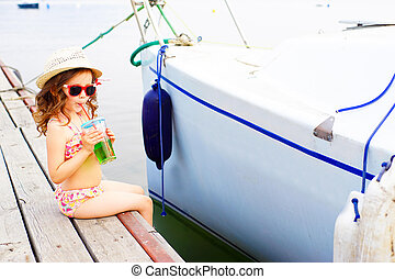 little girl drinking sparkling water on the pier