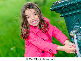 Little girl drinking water in a fountain
