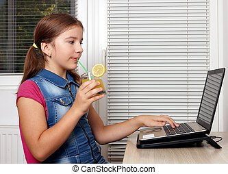 Little girl drinks juice and works on the laptop