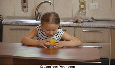 little girl drinks orange juice while sitting at the kitchen