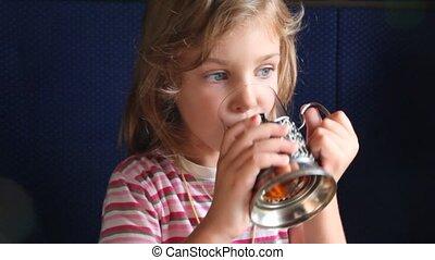 Little girl drinks tea in train. - Cute little girl in...