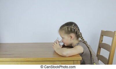 Little girl drinks water from a glass while