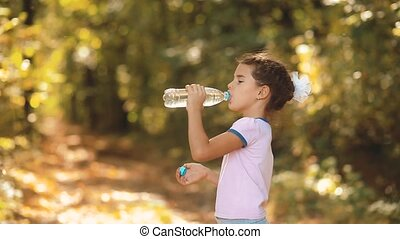 little girl drinks water from a plastic bottle in the autumn...