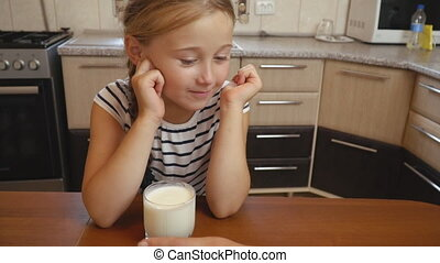 little girl drinks yogurt in the kitchen