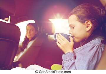 little girl driving in car and drinking from cup - family,...