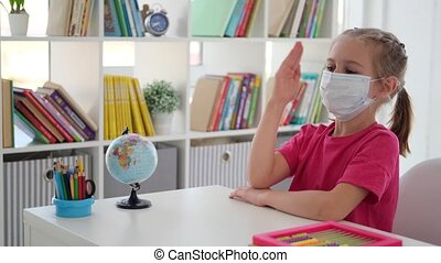 Little girl in mask eager to answer at school lesson during coronavirus pandemic