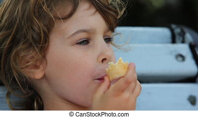 little girl eat ice cream and sit on bench at park