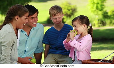 Little girl eating a green apple in front of her family