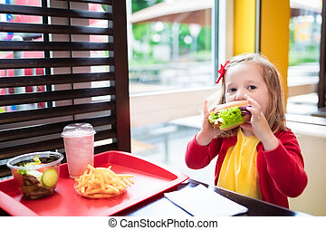 Little girl eating a hamburger in fast food restaurant