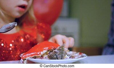 Little girl eating a strawberry cake