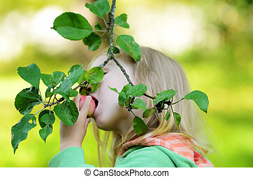 little girl eating an apple on a branch in garden
