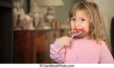 Little girl eating and licking with tongue big multicolor spiral lollipop candy