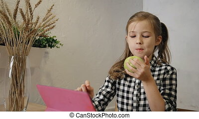Little girl eating apple and using tablet computer in the...