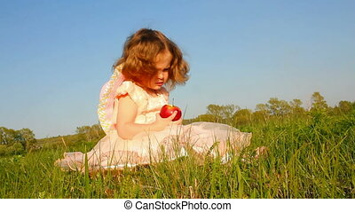 little girl eating apple on meadow