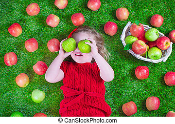 Little girl eating apples - Child eating apple. Little girl...
