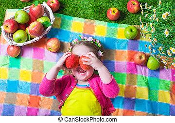 Little girl eating apples - Child eating apple. Little girl...