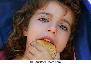 Little girl eating biscuit closeup portrait