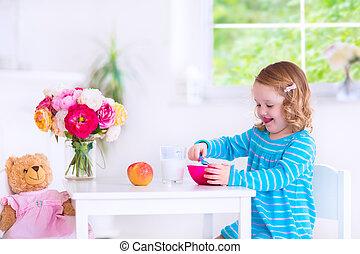 Little girl eating breakfast - Funny cute little girl in a ...