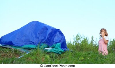 girl eating cake and looking at somebody fluttering in tent