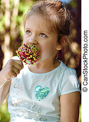 little girl eating candy apple