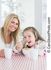 Little girl eating cereal at breakfast with her mother