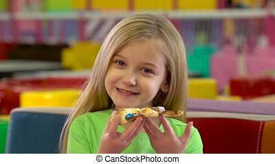 Little girl eating chocolate pizza during dinner at...